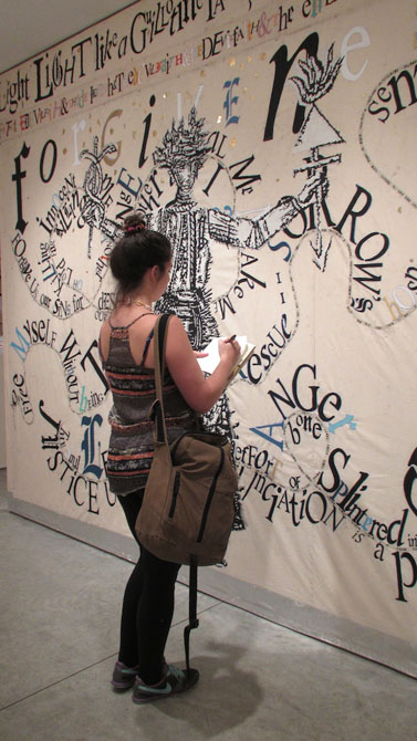 Student looks at art on wall