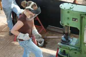 Female student in mask uses sculpture machinery