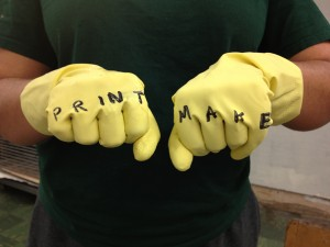 Close-up of yellow gloves with text written on fingers: PRINT MAKE
