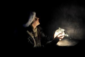 Student in dark room, holding light