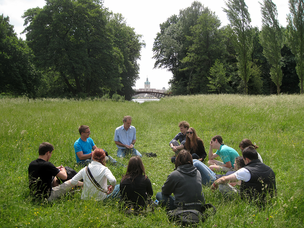 Students sitting in circle in grass field