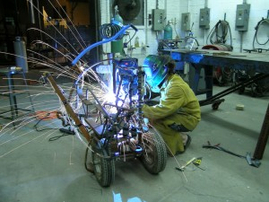Student welding in yellow suit and face mask, sparks flying