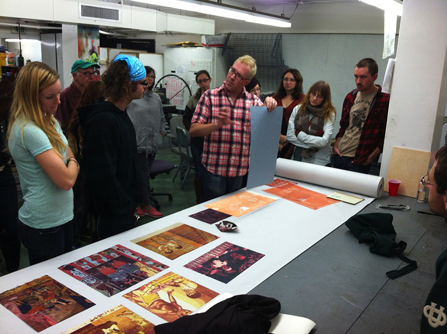 lsu printmaking students around table of prints