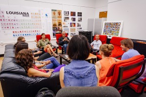 Students sit in red chairs around visiting artist.
