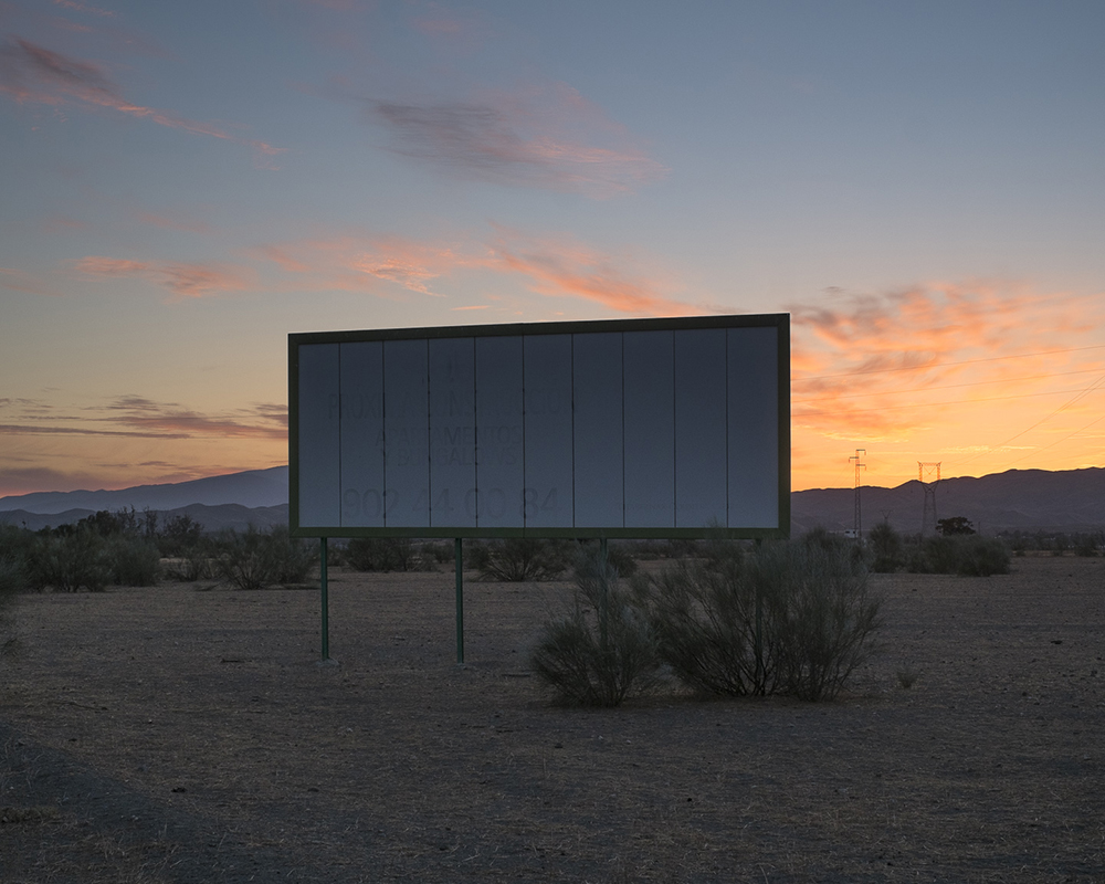 Billboard in desert, sunset in background. by Jeremiah Ariaz