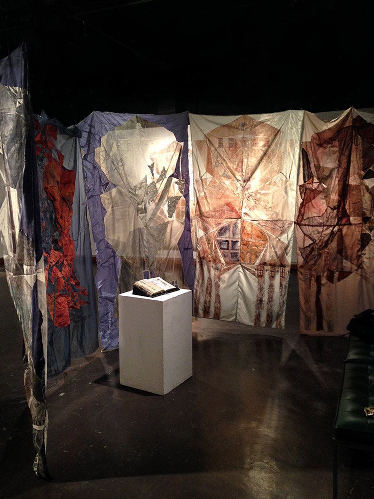Multicolored fabrics hang in black space, book on white podium. Molly Miller LSU MFA printmaking