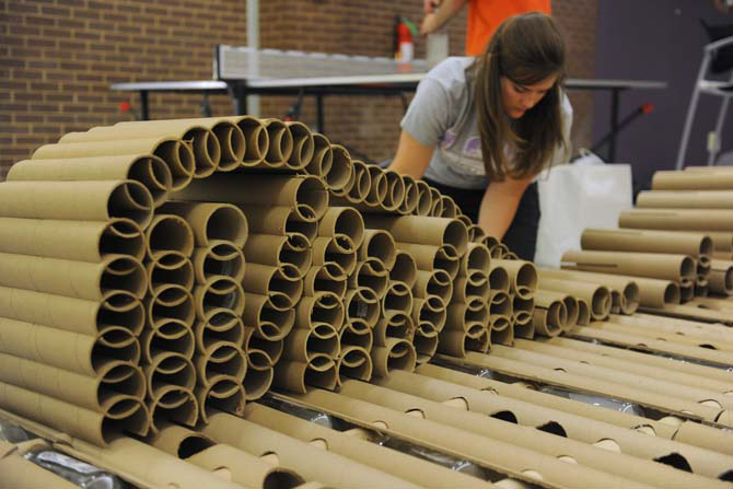 Young woman builds cardboard tube model, LSU ARCH 4041 Issues in Sustainability