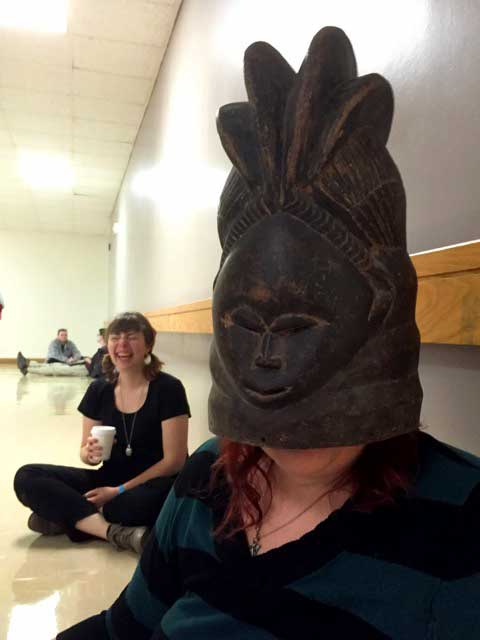 student in African mask