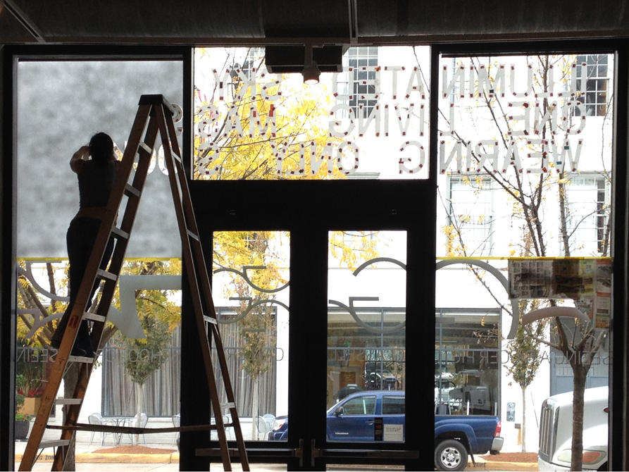 Person on ladder puts art on glass windows.