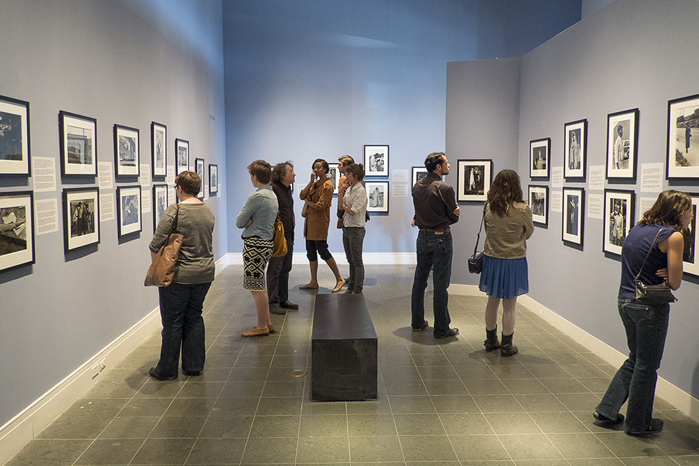 People study photography on walls in museum