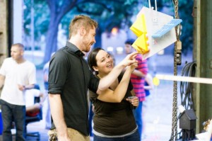 People smile and point at hanging sculpture at LSU school of art grad walk exhibition