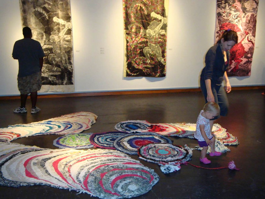 Woman and child explore art on floor in gallery. Hannah Campbell LSU MFA printmaking