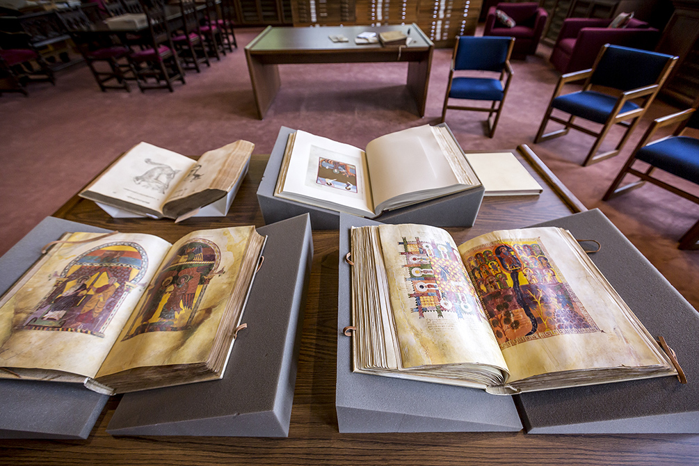 Old manuscripts with open pages displaying colorful illustrations