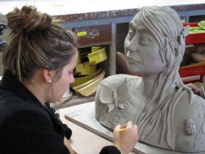 Student works on bust of woman