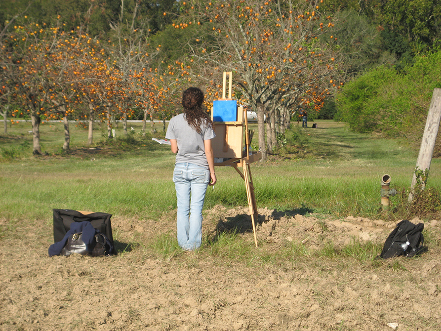 Student standing in field at easel