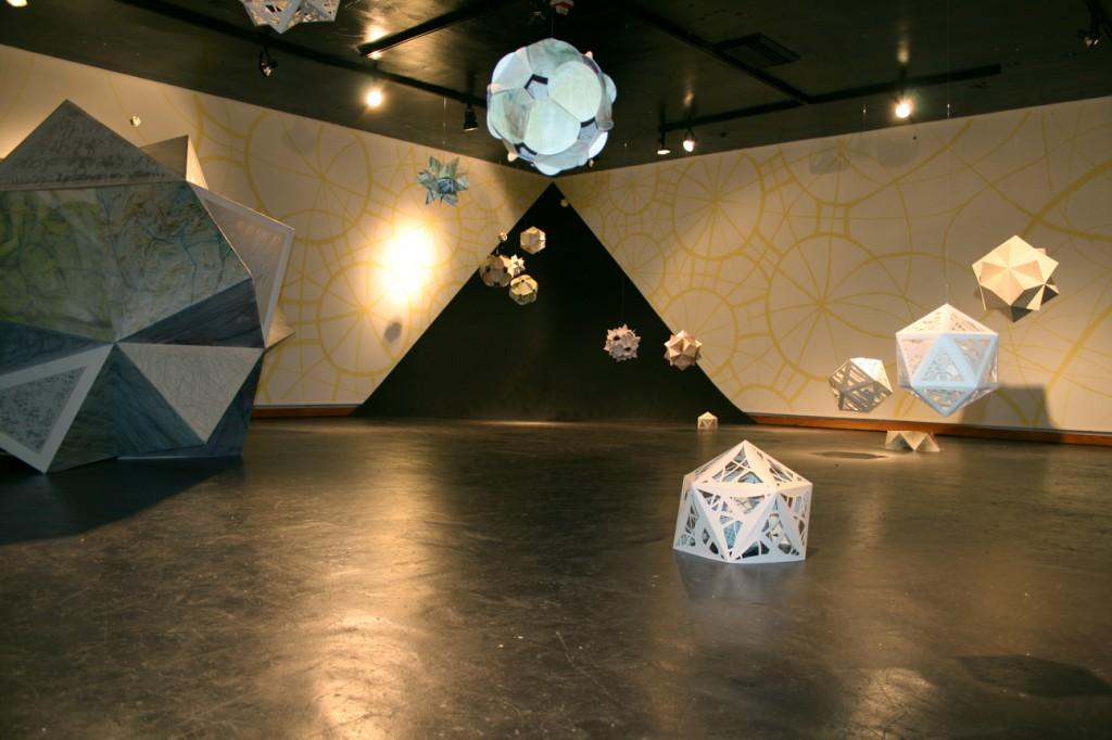Paper geometric sculptures suspended in room, and on floor. Rebecca Kreisler LSU MFA printmaking