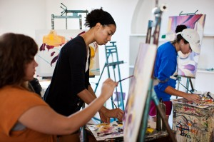Female African American student paints at easel in classroom