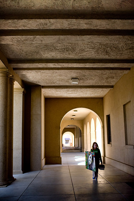 Student walking under portico along LSU Quad