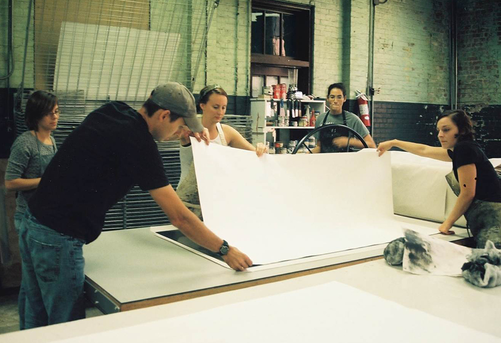 people pressing large paper
