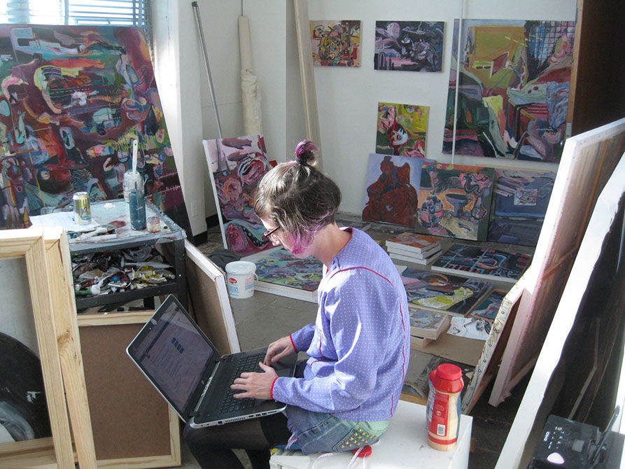 female student on laptop in studio, surrounded by paintings