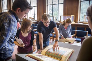 People gather around manuscripts in library