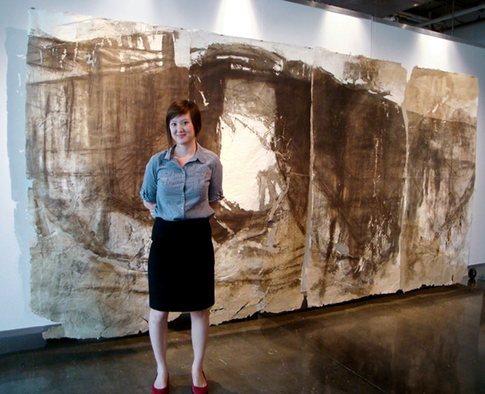 Young woman in front of large abstract brown print, May Babcock LSU MFA printmaking