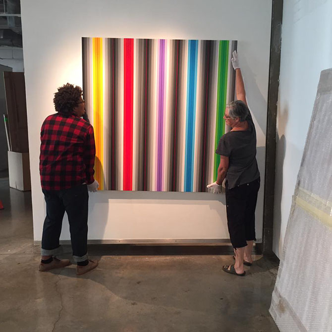 lsu glassell gallery, two people look at painting with colorful stripes