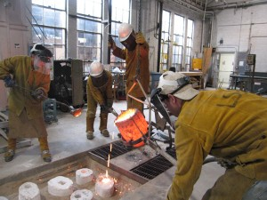lsu sculpture students in yellow suits and had hats pour a glowing vessel of liquid fire into containers on the floor