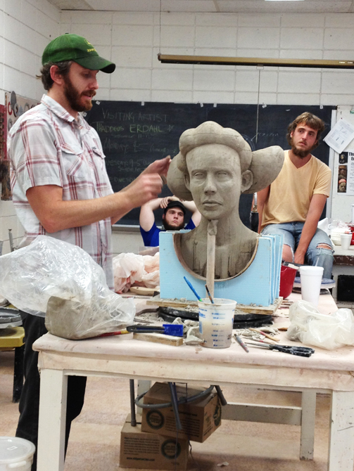 Male student with beard working on ceramic bust of person.