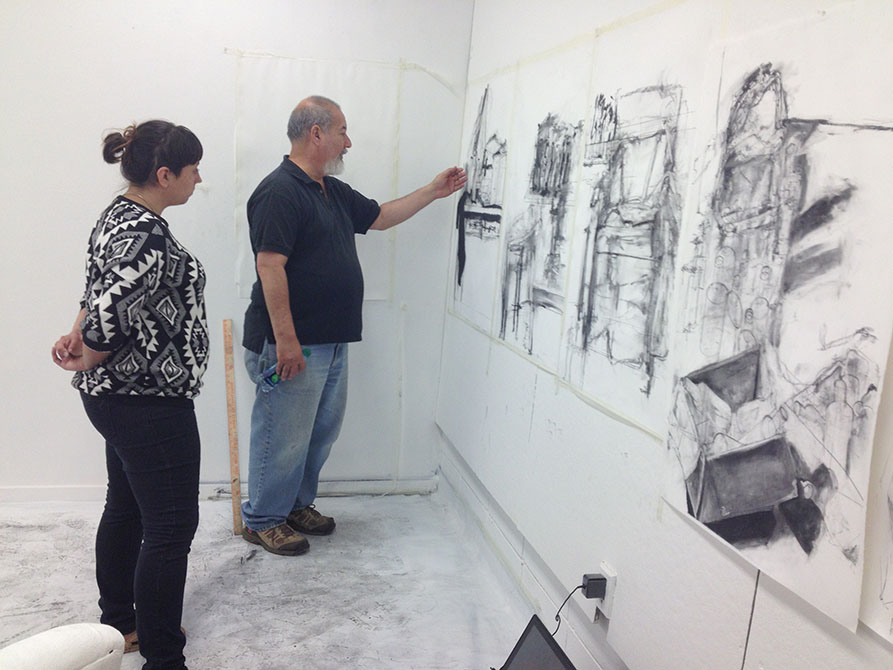man points to charcoal drawings on wall
