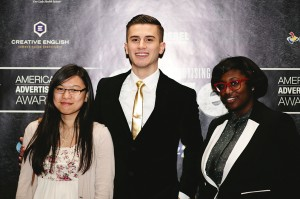 Three smiling students, American Advertising Awards logo on black wall behind