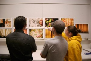 Students stare at photography prints on walls