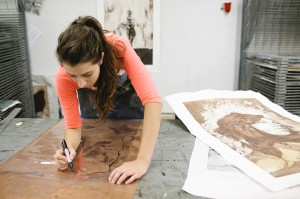 LSU printmaking student in pink shirt carves a design into a brown plate