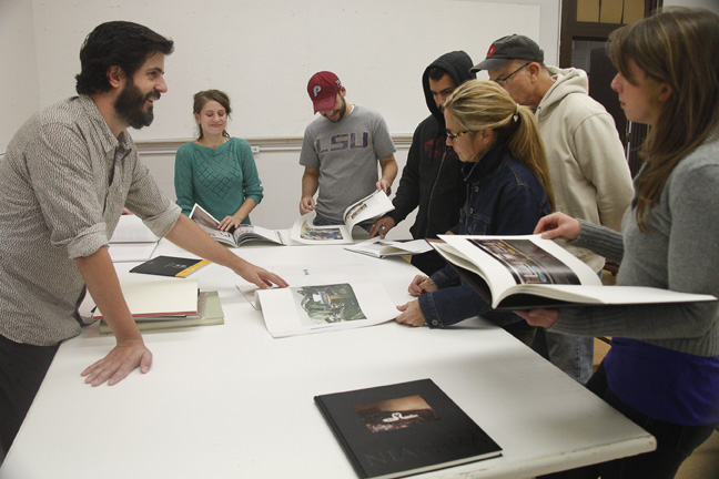 Students looks through photography books. lsu school of art visiting artists program