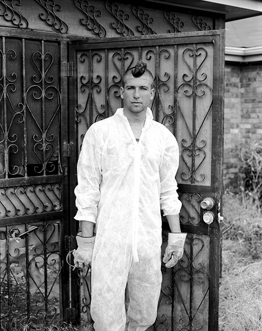 A man in work clothes stands by fence