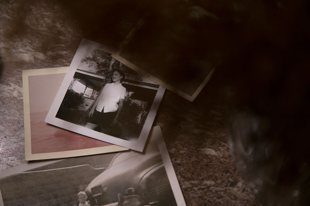 Old black and white photos lie on the floor