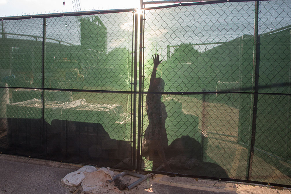 Outline of a woman is seen through a screen fence