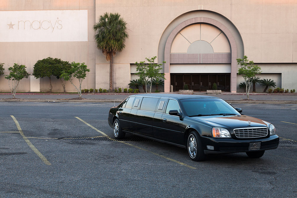 A limousine parked in front of an empty department store