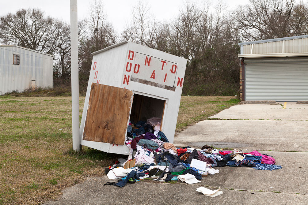 Clothes spill out of a donation box and onto the street