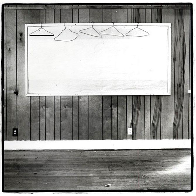 An empty whiteboard hangs on a wooden wall