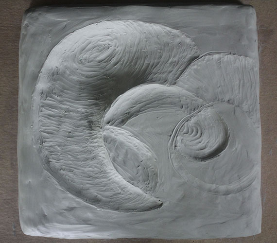 Clay study model of crescent surface patterns