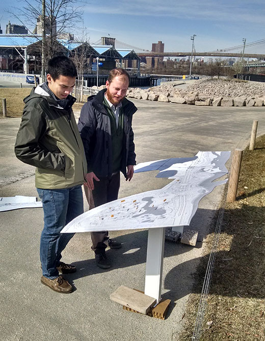 People in park studying site plan
