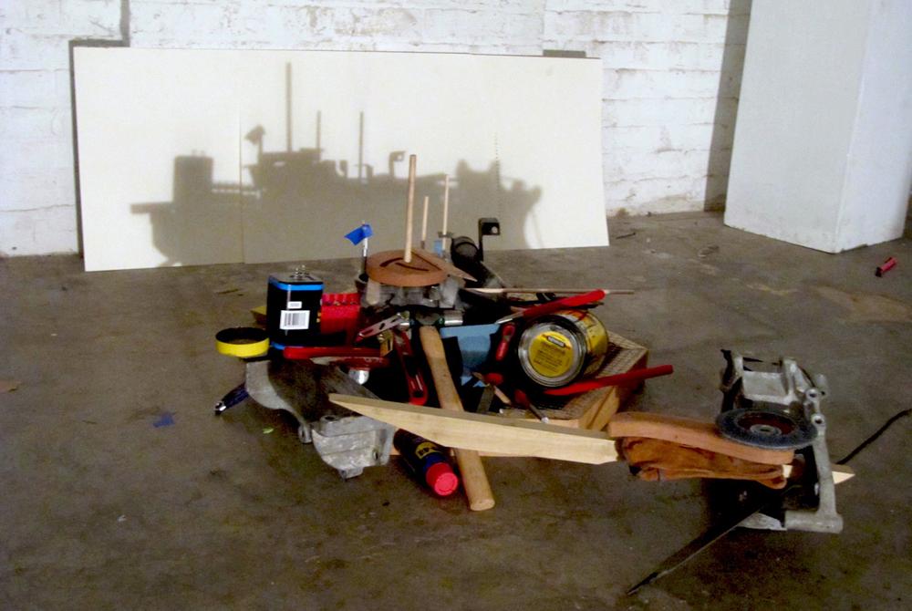 Assorted piled tools cast shadow shape of ship. LSU BFA Studio Art Sculpture