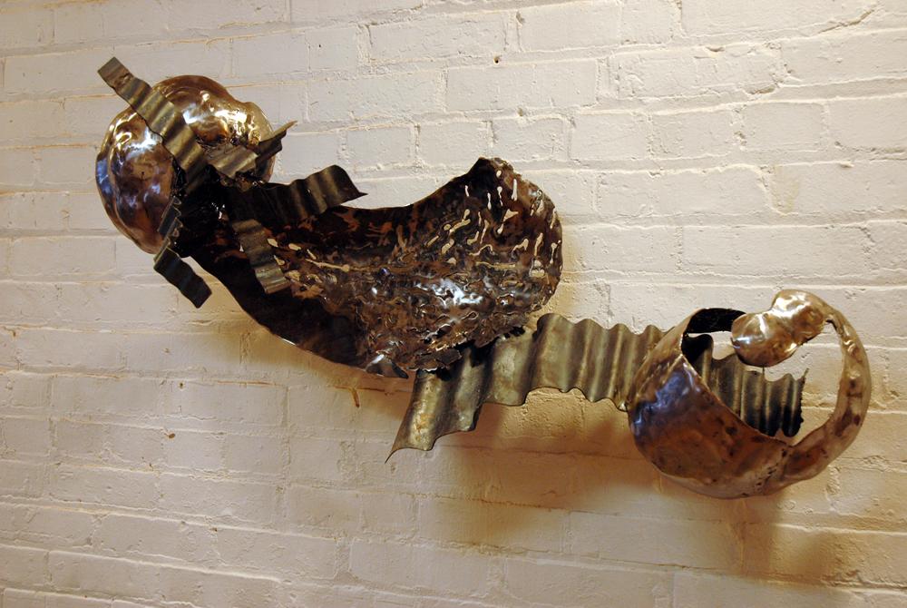 Shiny metal abstract sculpture on white brick wall. LSU BFA Studio Art Sculpture