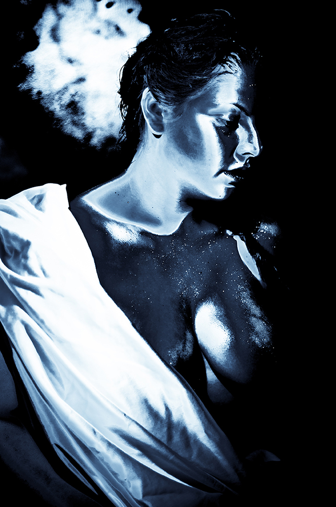 Woman with cloth draped over body, framed by shadows. LSU BFA Studio Art Photography
