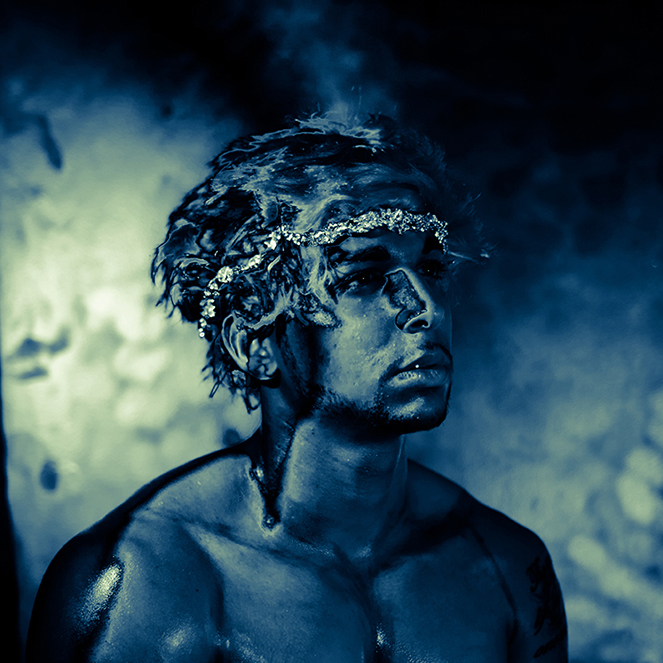 Image of young man in dark body paint