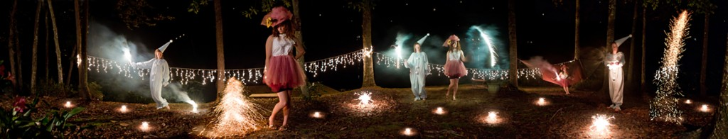 Panorama photo of people in costume, fire glowing in woods at night. LSU BFA Studio Art Photography