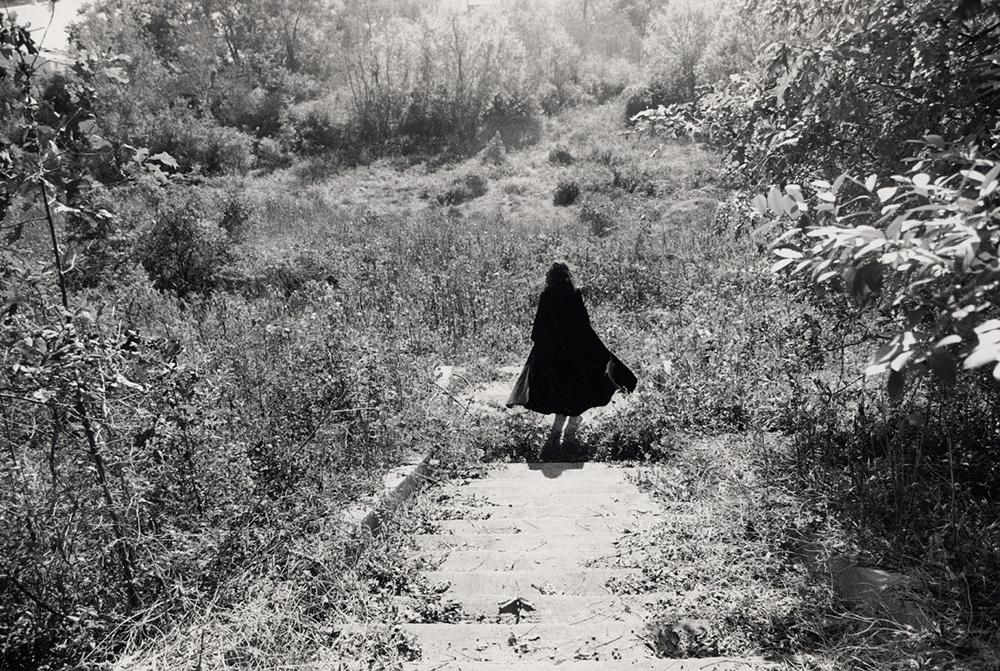 Woman in black coat in wild