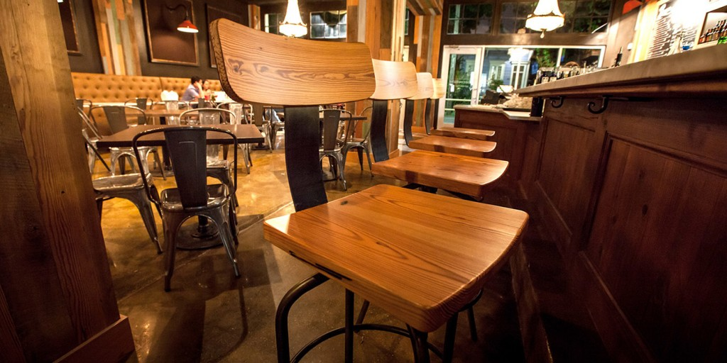 Restaurant interior with wood chairs, bar, modern tables