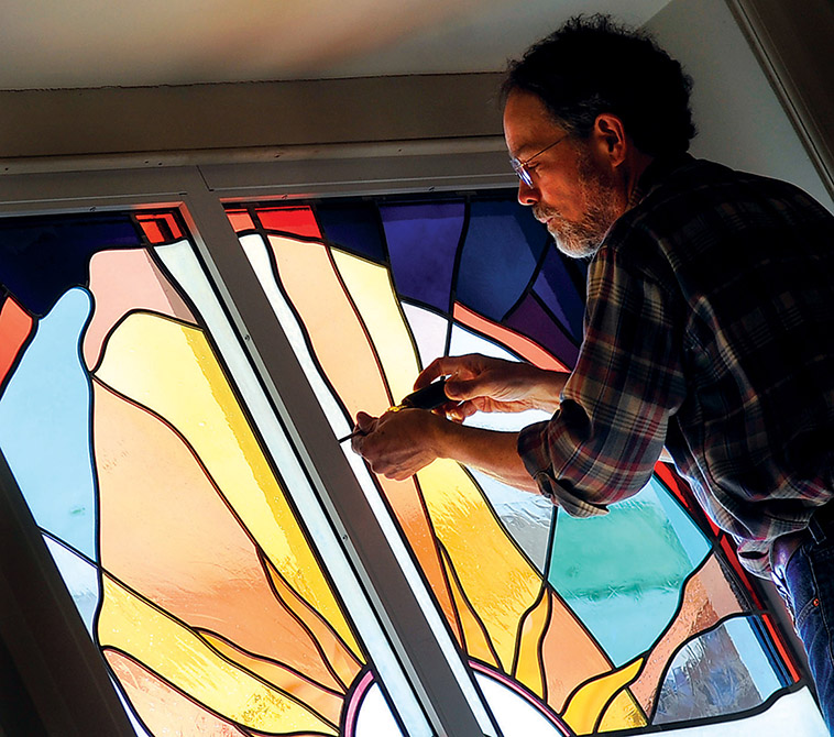 man works on stained glass